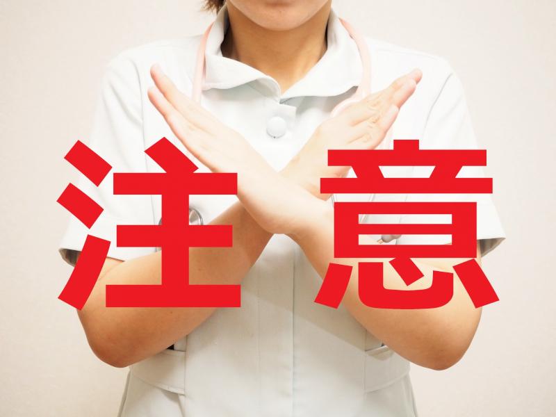 注意の赤い文字と両手でバツする女性