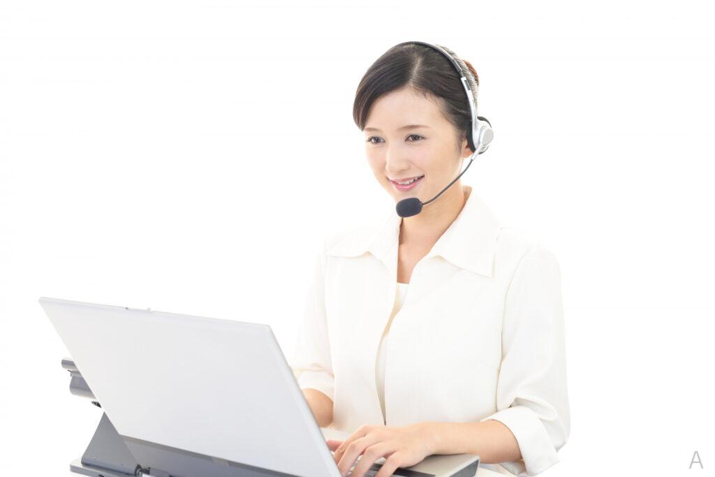 ヘッドセットを付けてパソコンを見る女性