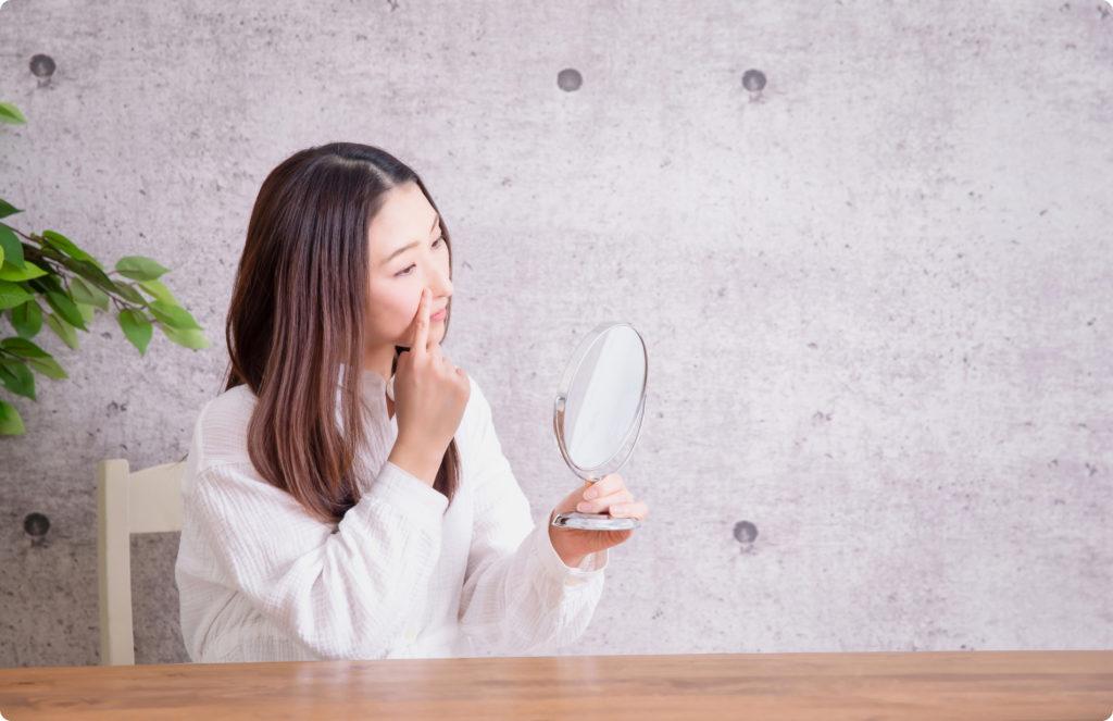 手鏡をもって肌を見る女性