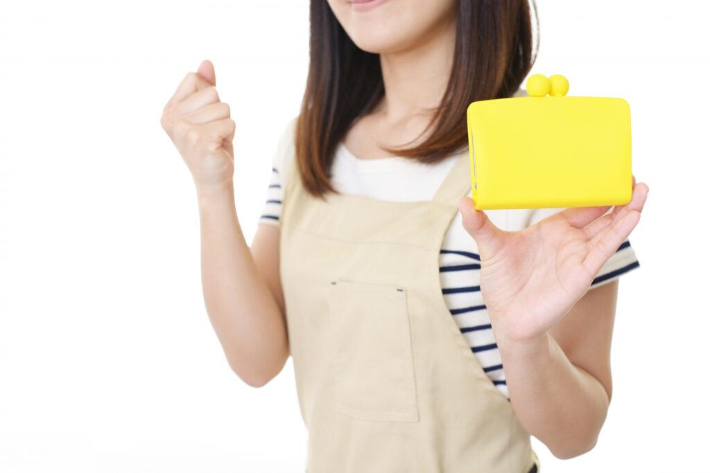 黄色い財布をもってガッツポーズをする女性
