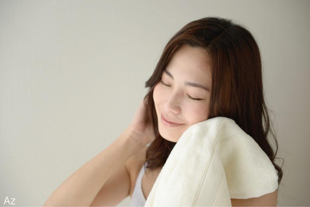 タオルで顔を拭く女性