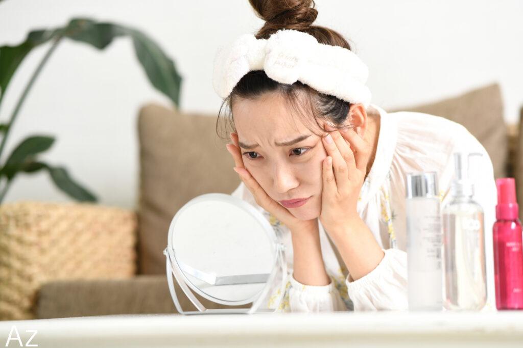 両手で頬をはさみ鏡をのぞき込む女性